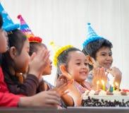 Группа в составе дети дуя именниный пирог в с днем рождениях петь дня рождения стоковое фото