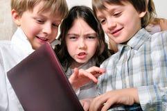 Группа в составе дети изучая на компьтер-книжке Стоковая Фотография