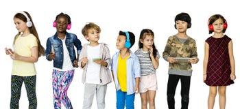 Группа в составе дети используя музыку приборов цифров слушая на белом Bla стоковое изображение
