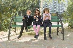 Группа в составе дети 7, 8 лет с мобильными телефонами, школьниками с рюкзаками смотря в смартфоны стоковая фотография
