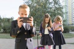 Группа в составе дети 7, 8 лет с мобильными телефонами, школьниками с рюкзаками смотря в смартфоны стоковые фото