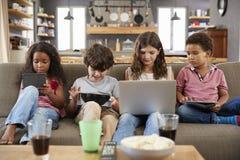 Группа в составе дети сидя на софе используя приборы цифров стоковое фото rf