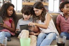 Группа в составе дети сидя на софе используя приборы цифров стоковые фотографии rf