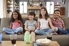 Группа в составе дети сидя на софе смотря телевидение совместно стоковая фотография rf