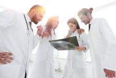 Группа в составе доктора обсуждая рентгеновский снимок Стоковое Изображение