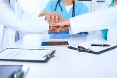 Группа в составе доктора соединяя руки на встрече Сыгранность и успех в медицине Стоковые Изображения RF