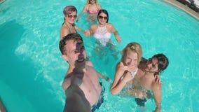 Группа в составе друзья делая selfie встречу в реальном маштабе времени в социальных средствах массовой информации в воде бассейн видеоматериал