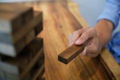 Группа в составе друзья играя игру блоков деревянную на таблице сложила pu стоковая фотография rf