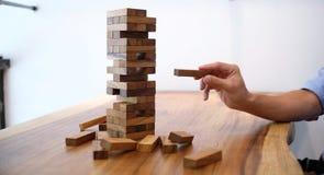 Группа в составе друзья играя игру блоков деревянную на таблице сложила pu Стоковое Изображение