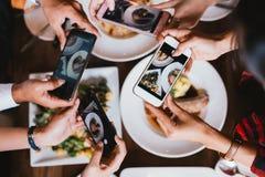 Группа в составе друзья идя вне и принимая фото итальянской еды вместе с мобильным телефоном стоковая фотография rf