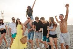 Группа в составе друзья идя на пляж, имеющ потеху, автожелезнодорожные перевозки женщины дальше укомплектовывает личным составом, стоковые фото