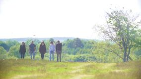 Группа в составе друзья идя outdoors идет от леса в летнем дне видеоматериал