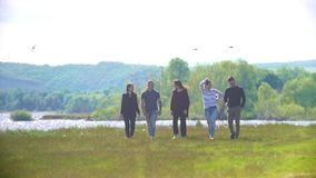 Группа в составе друзья идя outdoors на поле и говорить лета видеоматериал