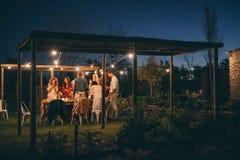 Группа в составе друзья имея официальныйо обед outdoors Стоковые Фотографии RF