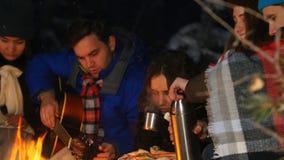 Группа в составе друзья имея полезного время работы огнем в древесинах Иметь заедк Молодой человек настраивая гитару акции видеоматериалы