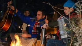 Группа в составе друзья имея полезного время работы огнем в древесинах Молодой человек открытый вверх по thermos акции видеоматериалы