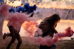 Группа в составе друзья имея потеху с бенгальскими огнями цвета закоптелыми на заходе солнца стоковое фото