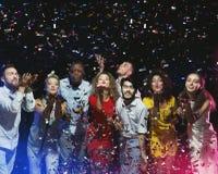Группа в составе друзья наслаждаясь партией и дуя confetti стоковое фото rf