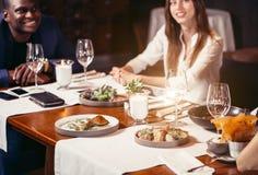 Группа в составе друзья наслаждаясь ужином на ресторане стоковая фотография rf