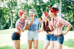 Группа в составе друзья на парке имея партию потехи Жизнерадостные девушки с торты в руках ретро тип Стоковые Фотографии RF