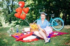 Группа в составе друзья на парке имея партию потехи Красивая девушка с gif в руках на пикнике Стоковые Изображения