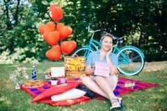 Группа в составе друзья на парке имея партию потехи Красивая девушка с gif в руках на пикнике Стоковое Изображение