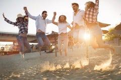 Группа в составе друзья на пляже имея потеху Стоковые Фотографии RF