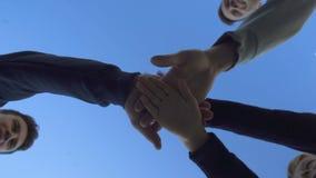 Группа в составе друзья положила руки совместно, команда работа водит к победе, нижний взгляд видеоматериал