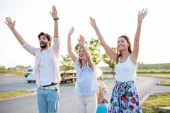 Группа в составе друзья путешествуя автостопом на стороне дороги стоковое фото