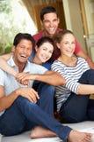 Группа в составе друзья сидя вне дома Стоковые Фото