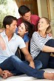 Группа в составе друзья сидя вне дома Стоковая Фотография