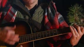 Группа в составе друзья сидя в лесе зимы огнем Молодой человек играя гитару сток-видео