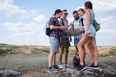 Группа в составе друзья смотря карту и обсуждая outdoors Друзья идут на пеший туризм, лес, воссоздание, любят активный образ жизн стоковое изображение
