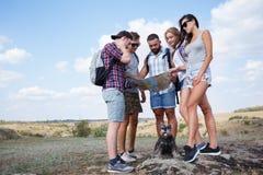 Группа в составе друзья смотря карту и обсуждая outdoors Друзья идут на пеший туризм, лес, воссоздание, любят активный образ жизн Стоковые Фото