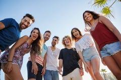Группа в составе друзья стоя совместно смеясь над outdoors Стоковые Фото