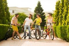 Группа в составе друзья с велосипедами смеется над Стоковые Изображения