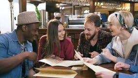 Группа в составе друзья хипстера читая меню и выбирая блюда в баре, пабе сток-видео