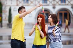 Группа в составе 3 друз идя в город есть мороженое, jok Стоковое фото RF