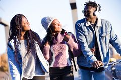 Группа в составе 3 друз идя и смеясь над в улице Стоковое фото RF