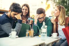Группа в составе 4 друз имея потеху кофе совместно внутри Стоковое фото RF