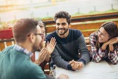 Группа в составе 4 друз имея потеху кофе совместно Стоковое фото RF