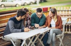 Группа в составе 4 друз имея потеху кофе совместно Стоковая Фотография