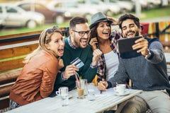 Группа в составе 4 друз имея потеху кофе совместно Стоковые Фотографии RF