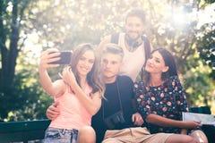 Группа в составе 4 друз принимая selfie с умным телефоном Стоковые Изображения RF