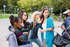 Группа в составе девушки будучи угрожанным с оружием разбойником Стоковая Фотография