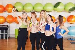 Группа в составе девушки в классе фитнеса делая selfi Стоковое фото RF