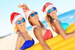 Группа в составе девушки в шляпах Санты имея потеху на пляже Стоковое Изображение