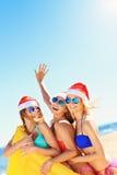 Группа в составе девушки в шляпах Санты имея потеху на пляже Стоковые Фото