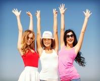 Группа в составе девушки охлаждая на пляже Стоковые Изображения