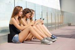 Группа в составе 3 девушки подростка печатая на мобильном телефоне